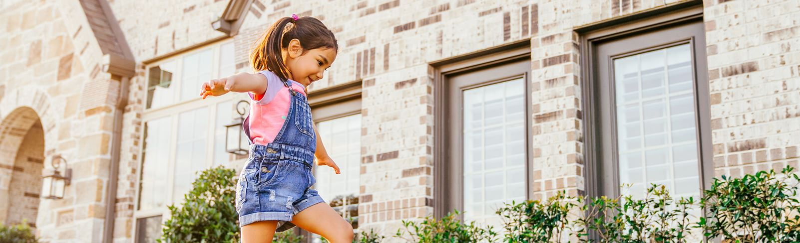 Girl walking outside of new home in Katy TX at Elyson community