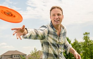 Man playing Frisbee outside of new home in Katy, Texas at Elyson community